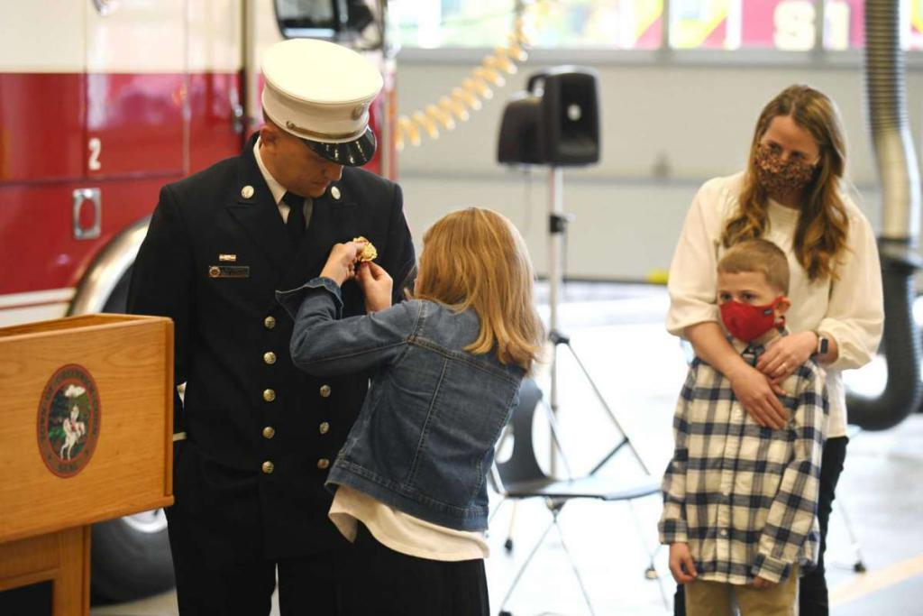 Tyler Sizemore / Hearst Connecticut Media Eric Maziarz receives his pin from his daughter, Caroline, as he is promoted to Deputy Fire Chief at the Public Safety Complex in Greenwich, Conn. Monday, Oct. 26, 2020.