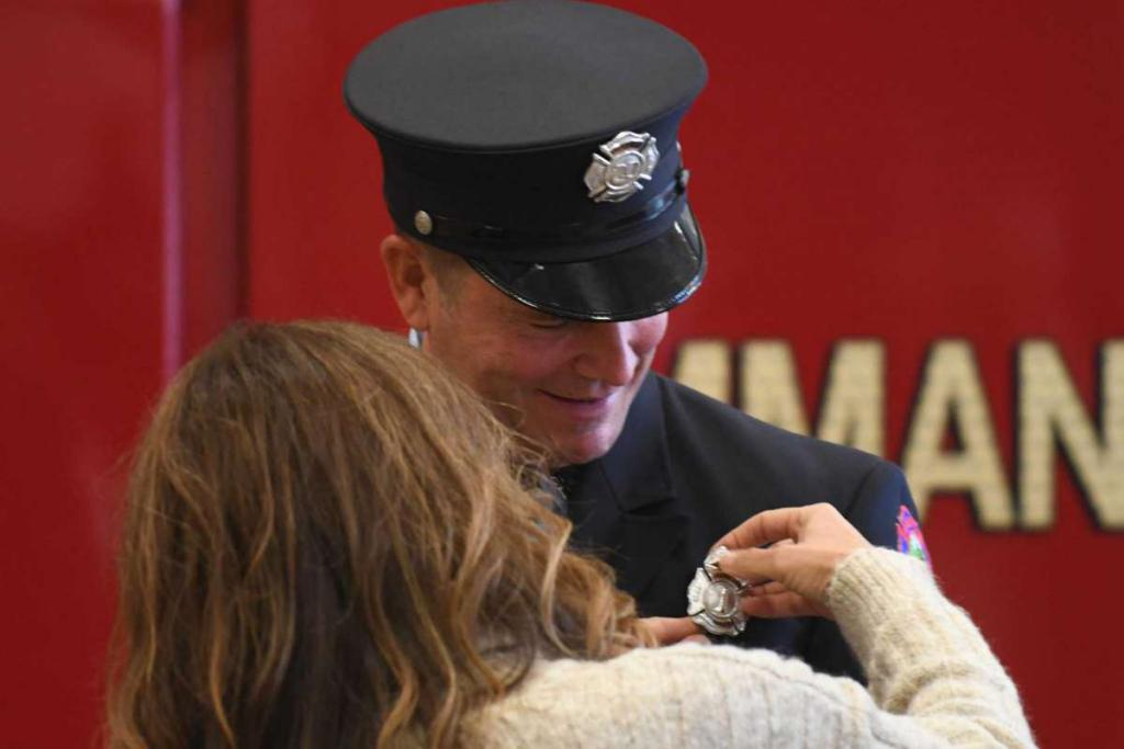 Tyler Sizemore / Hearst Connecticut Media Mike Wilson receives his pin from his wife, Gabriella, as is promoted to Fire Lieutenant at the Public Safety Complex in Greenwich, Conn. Monday, Oct. 26, 2020.